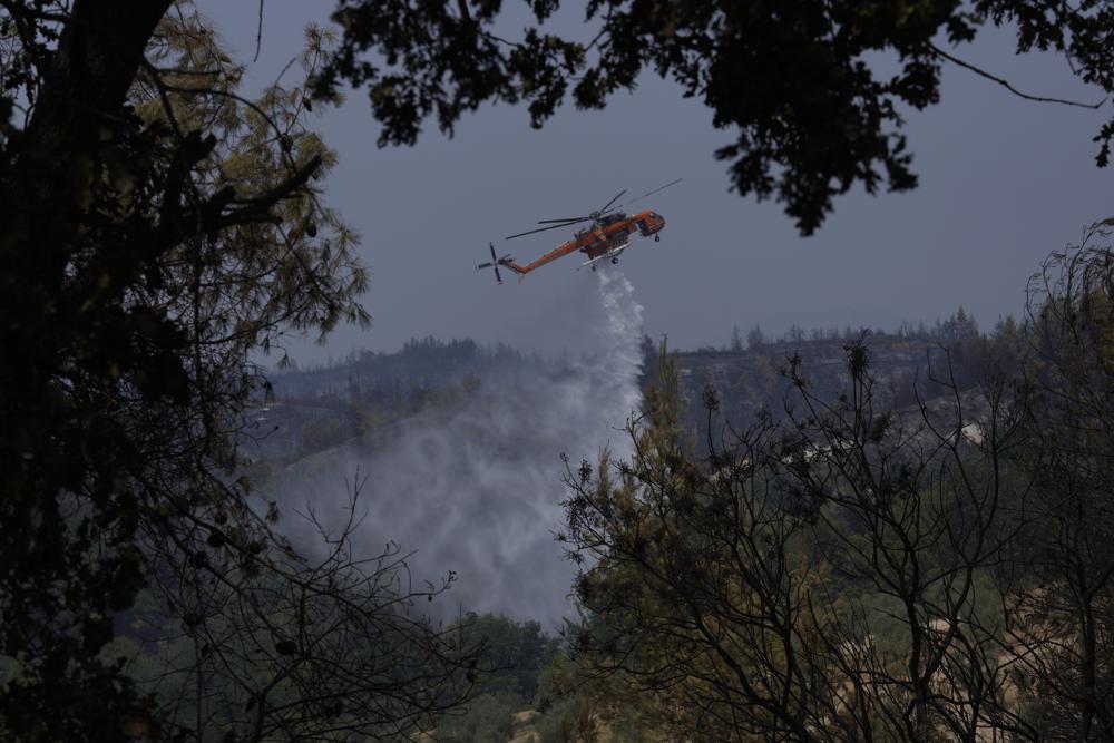 Aviones y helicópteros con agua intentan apagar los restos de fuego en Grecia. - Foto Petros Karadjias/AP